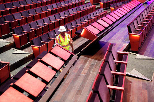 Workers try to get the chairs on the bottom level of the H-E-B Performance Hall to go underneath the floor Aug. 20, 2014 as they try to get it to a flat floor inside the Tobin Center for the Performing Arts for its opening date of Sept. 4, 2014. Photo: CYNTHIA ESPARZA, FOR THE SAN ANTONIO EXPRESS-NEWS / FOR THE SAN ANTOINO EXPRESS-NEWS