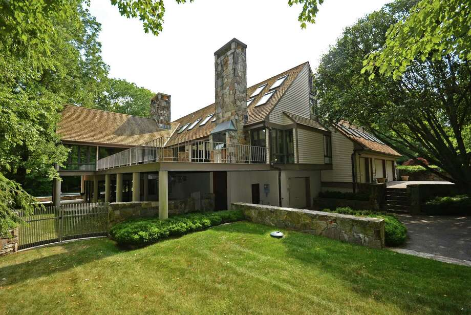 The grey-green clapboard home at 365 West Road in New Canaan is surrounded by 2.6 acres of landscaping, lush in Renaissance gardens filled with asters, iris, ferns and grasses. It is on the market for $2,695,000. Photo: Contributed Photo, Contributed / New Canaan News Contributed