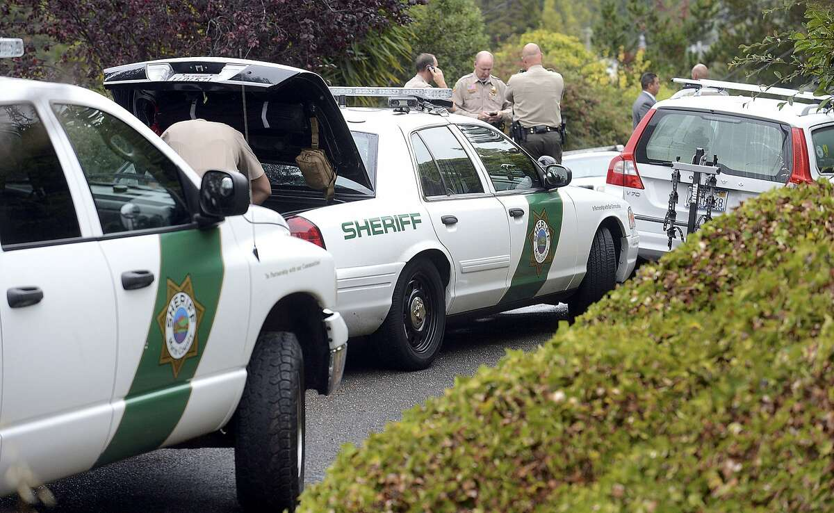 Marin County Sheriff's detectives investigate the shooting deaths of two men in neighboring backyards on Carlota Circle in the Strawberry neighborhood of Mill Valley, Calif., Thursday, Aug. 21, 2014.