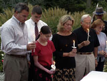 Gov. John G. Rowland, left and his wife Patti, fourth from left, stand with office staff members between them Marrissa Najarian, from Hartford, and Michael Bright, at rear, from Newington, along with former Lt. Gov. Joseph Fauliso and his wife Ann at far right, hold candles for the Tribute of Light across America in a moment of silence in  remembrance of the victims of the terrorist attacks of two years ago, outside the Governor's Residence in Hartford, Conn., Thursday, Sept. 11, 2003.