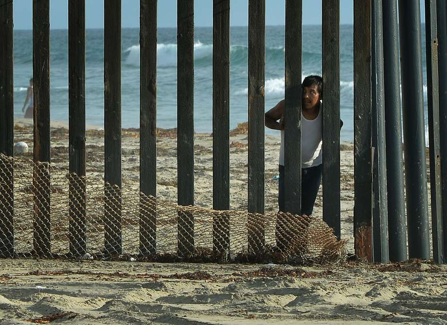 On the other side of the land of opportunity:A man looks out towards the United States from the Mexican side of the border fence that divides 