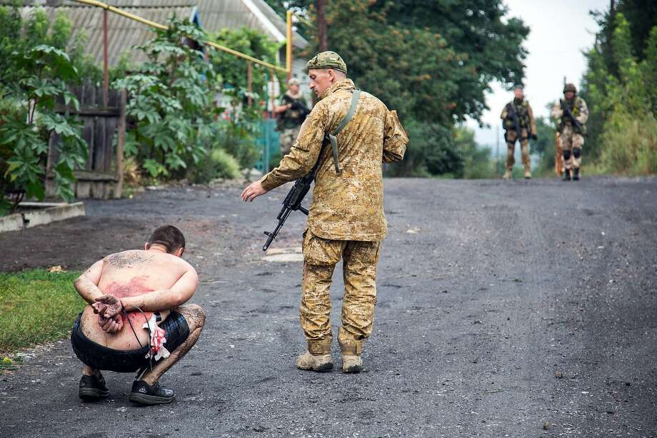 Wounded prisoner:A Ukrainian soldier detains a pro-Russian militant in the village of Chornukhine after a Ukrainian warplane was blown out of the sky over rebel-held territory. Fierce clashes between   government troops and pro-Russian insurgents left dozens of civilians dead. Photo: Oleksandr Ratushniak, AFP/Getty Images