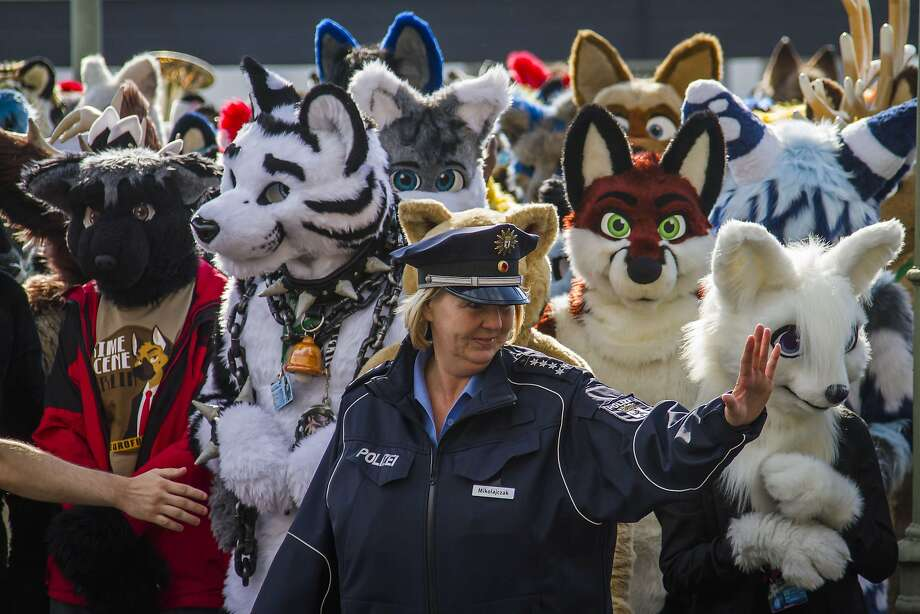 "Europe's cuddliest converge in Germany: In Berlin, a police officer halts traffic to allow delegates to Eurofurence, ""Europe's biggest furry convention"" to cross to the conference hotel. Photo: Odd Andersen, AFP/Getty Images"