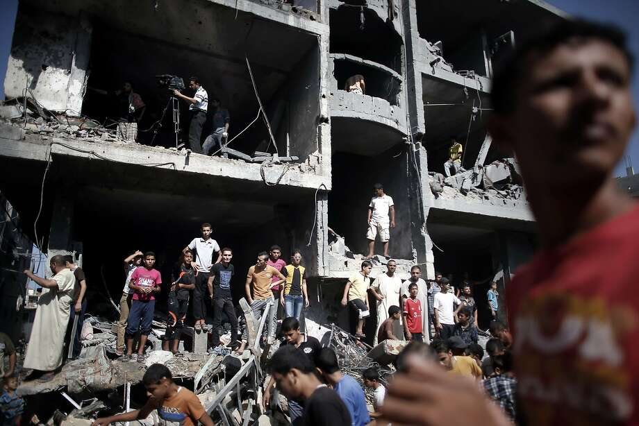 Palestinians gather around the rubble of a building destroyed in an Israeli air strike in Gaza city of Rafah. Photo: Thomas Coex, AFP/Getty Images