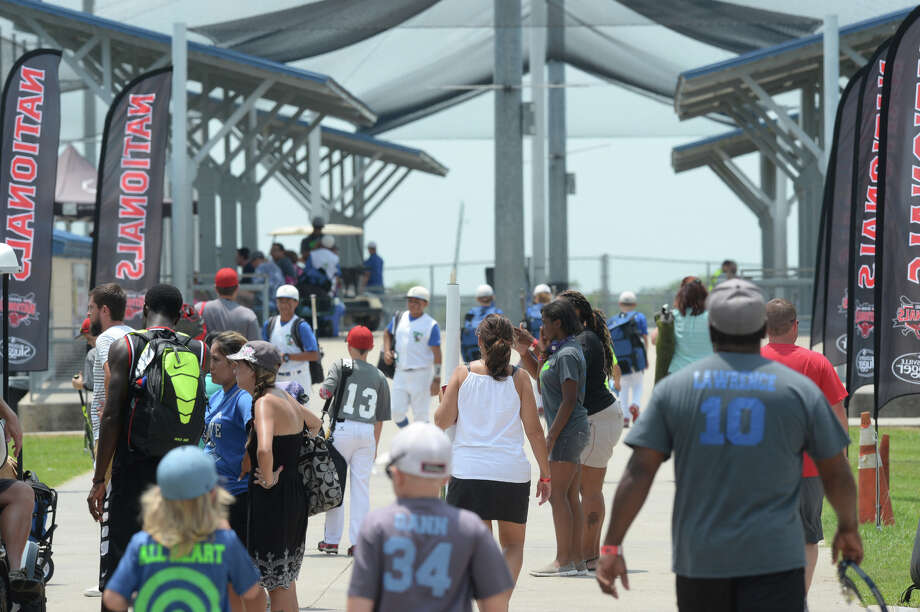 Fans, athletes and family members walk between the fields during the Nationals baseball tournament at Ford Park on Monday. Photo taken Monday, July 21. 2104 Guiseppe Barranco/@spotnewsshooter Photo: Guiseppe Barranco, Photo Editor