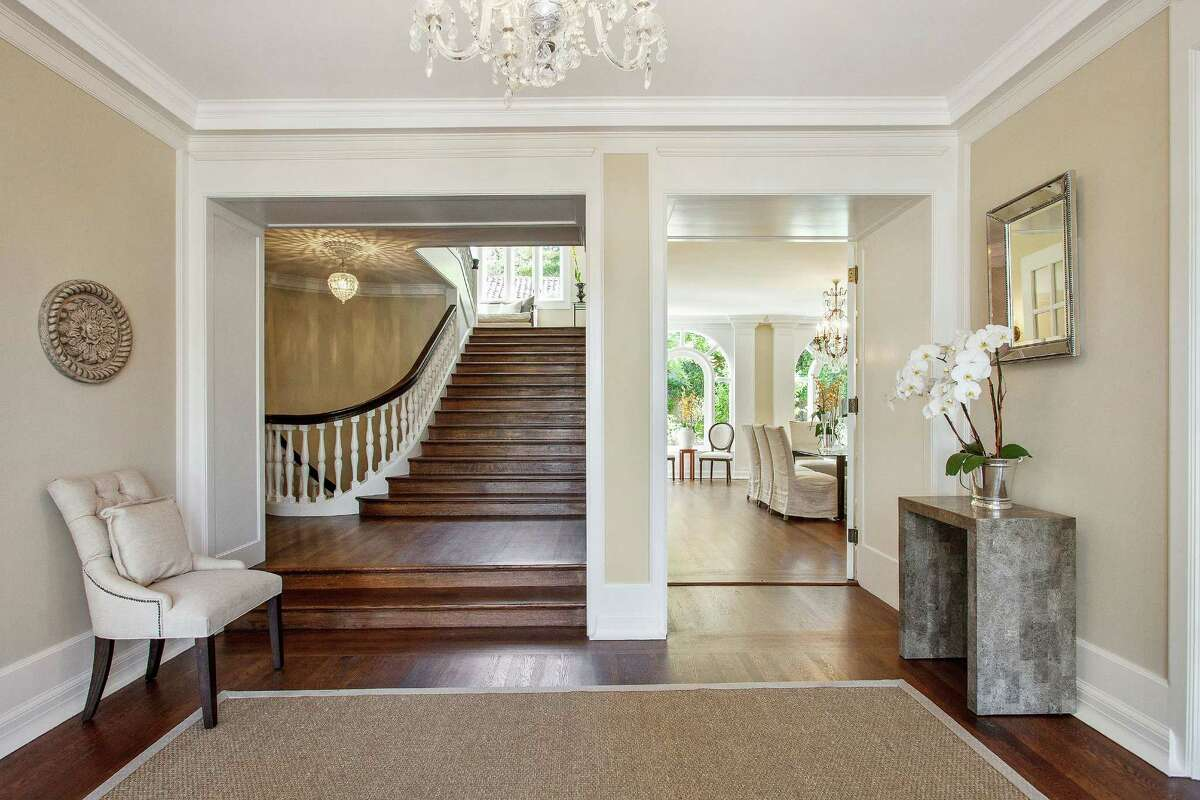 The entrance hall is illuminated by a chandelier and leads to a curved, hardwood staircase.