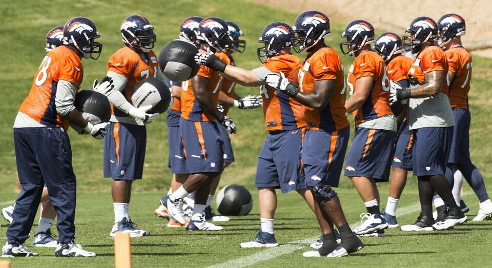 Broncos offensive linemen throw medicine balls back and forth.