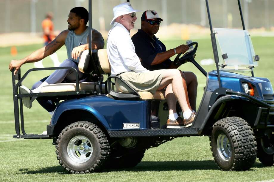 Texans running back Arian Foster, left, rides off the practice field on a golf cart with Texans owner Bob McNair. Photo: Brett Coomer, Houston Chronicle