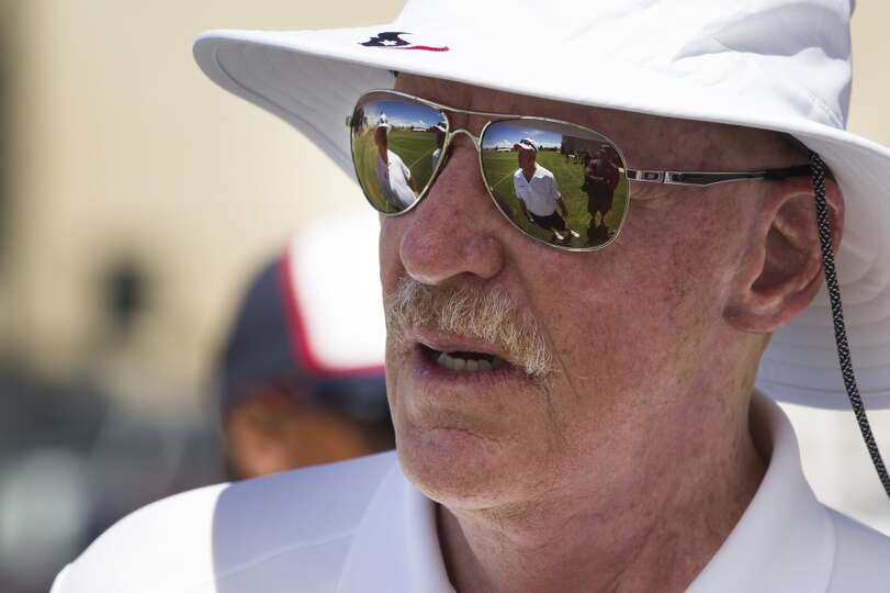 Texans owner Bob McNair speaks to Broncos head coach John Fox, reflected in his sunglasses.