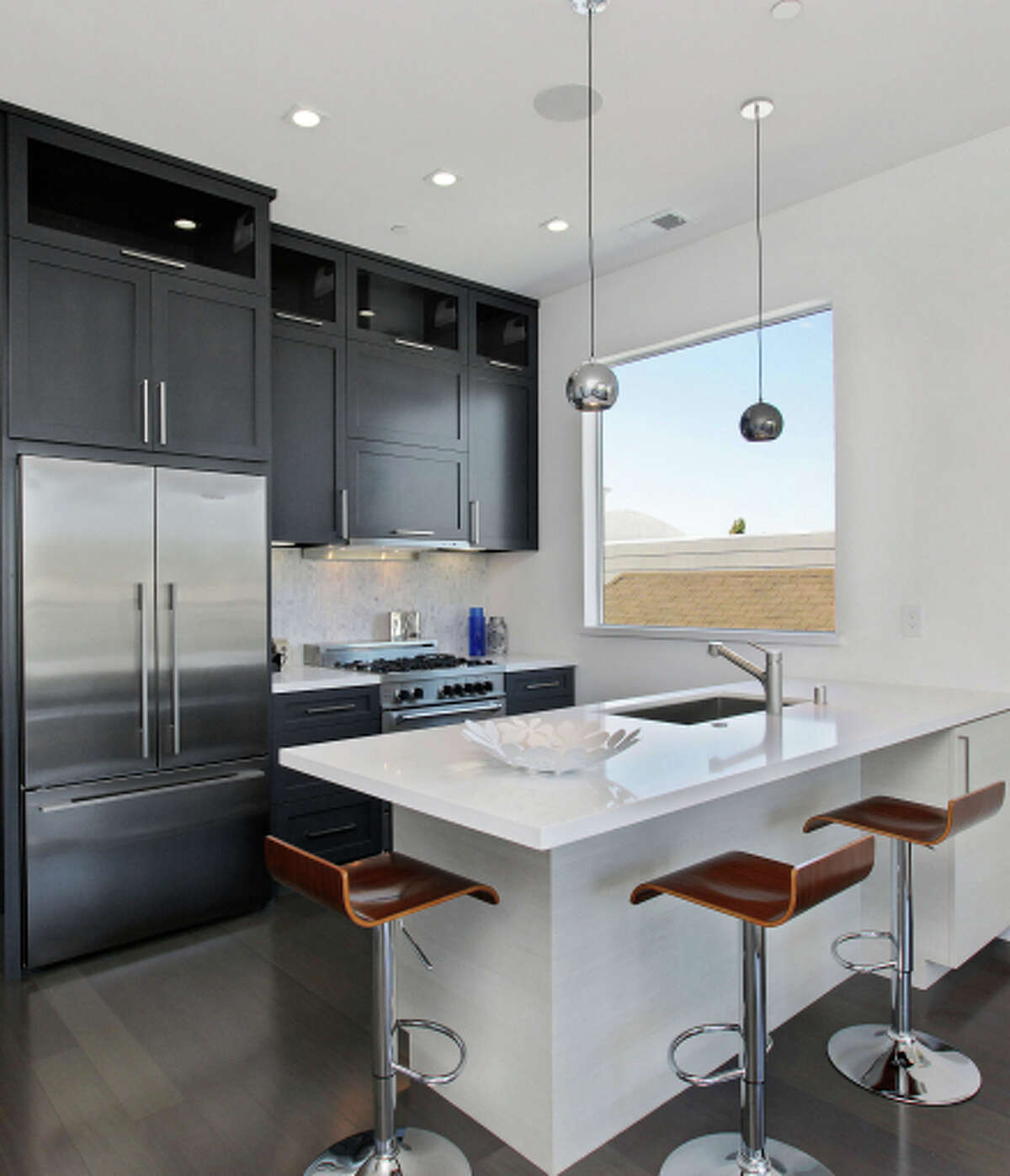 The kitchen hosts a Bertazzoni range and a breakfast bar beneath pendant lights.