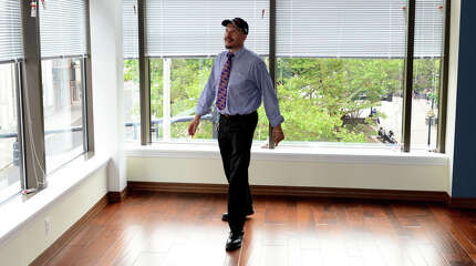 Christopher Petre, an estimator with Viking Construction, checks out one of the apartments available in the new renovation inside the former Mechanics & Farmers Bank building in downtown Bridgeport, Conn. on Thursday, Aug. 21, 2014.