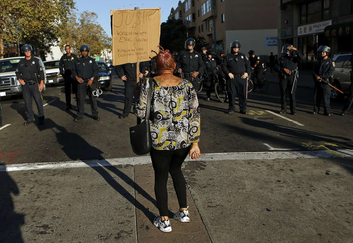 LaNora Anderson confronts a lone of Oakland Police at 8th and Broadway while taking part in a protest in support of Ferguson, Missouri residents in Oakland, Calif. on Wednesday, August 20, 2014.