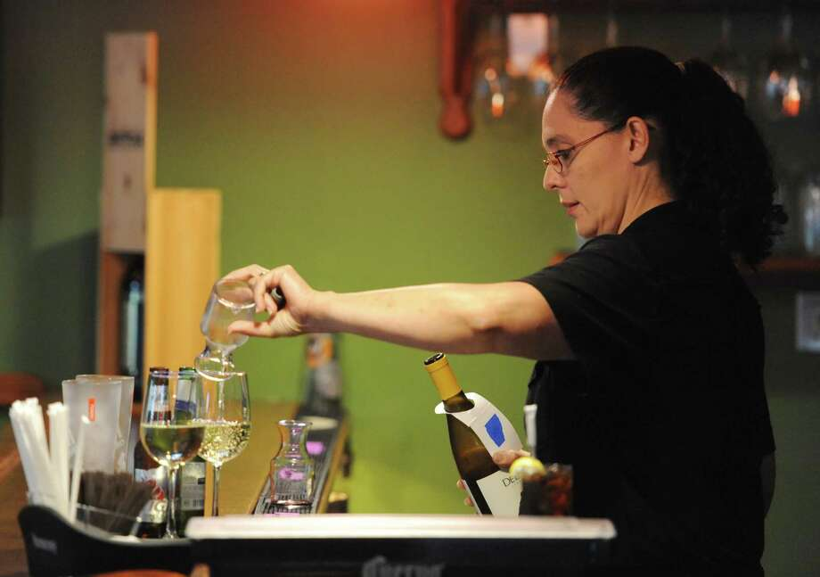 Waitress Janet Sotelo pours a glass of wine in the bar of Aranci 67 in the Georgetown section of Redding, Conn. Wednesday, Aug. 20, 2014.  The town of Redding has seen significant job growth since the recession with the food service industry leading the way. Photo: Tyler Sizemore / The News-Times