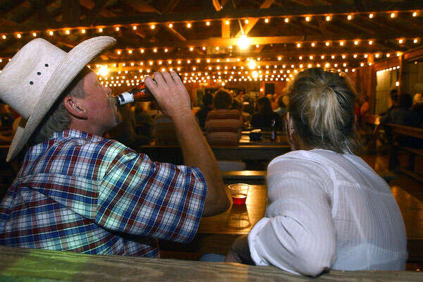Cotton Sultemeier quenches his thirst  as he enjoys the evening in the Luckenbach Dance Hall with friend Susanne Frenzel.