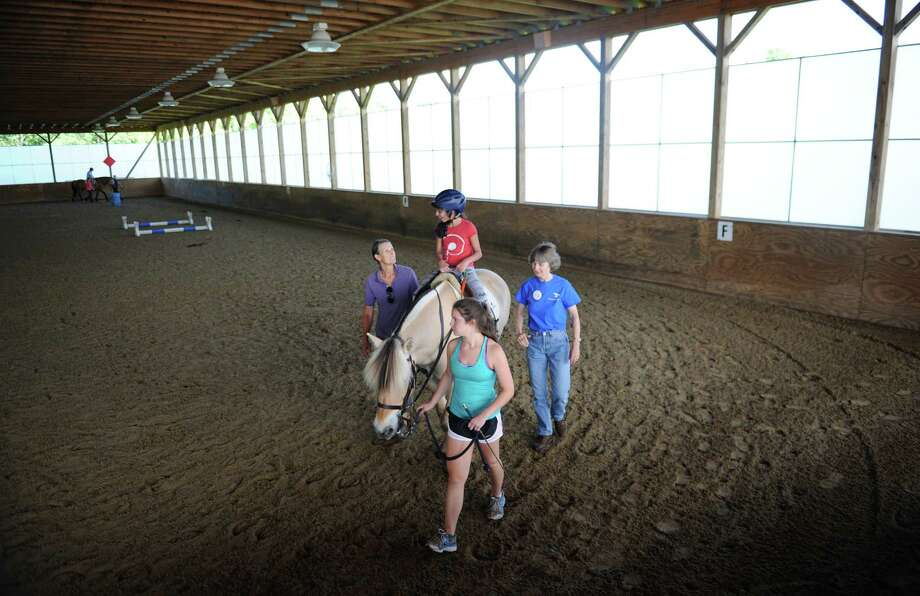 Julia Brandeis, 13, of Rye Brook, N.Y., rides a horse with assistance from volunteers Judy Burke, left, Samantha Kirsch, front, and Barbara Reed at Pegasus Therapeutic Riding in Brewster, N.Y. Thursday, Aug. 14, 2014.  Pegasus is a 20-acre horse farm and riding center that provides lessons and camps to those with special needs in the area. Photo: Tyler Sizemore / The News-Times