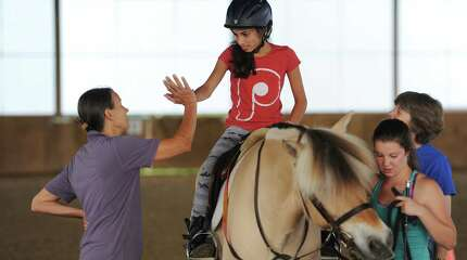 Rider Julia Brandeis, 13, of Rye Brook, N.Y., high-fives volunteer Judy Burke, left, after riding at Pegasus Therapeutic Riding in Brewster, N.Y. Thursday, Aug. 14, 2014.  Pegasus is a 20-acre horse farm and riding center that provides lessons and camps to those with special needs in the area.