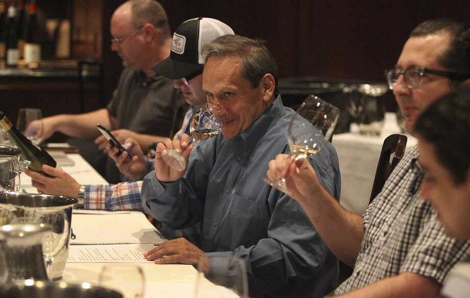 Eric Rodnite (center) samples a Riesling wine. A theme set each month determines the wine. Photo: Photos By John Davenport / San Antonio Express-News / ©San Antonio Express-News/John Davenport