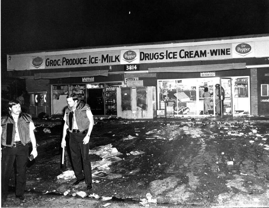 One Year Later: The Moody Park RiotsTwo Houston police officers stand guard over a wrecked convenience store at 3814 Fulton. Looters struck the store during a riot that began at Moody Park.  Photo: Mike Robinson, © Houston Chronicle / Houston Chronicle