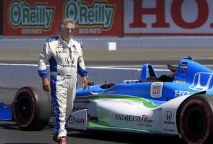 Mario Andretti walks past his two-seater Indy car before driving Chronicle sports writer Tom FitzGerald on a lap around the Sonoma Raceway track in Sonoma, Calif. on Thursday, Aug. 21 2014. The GoPro Grand Prix of Sonoma is this Sunday.