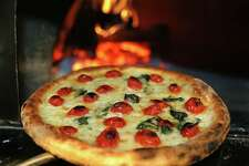 A Parma Pizza, without it's final toppings, comes out of the wood-burning oven at Va Bene, the newest pizzeria concept from the family that own the Luciano Restaurants. Tuesday, Aug. 19, 2014.