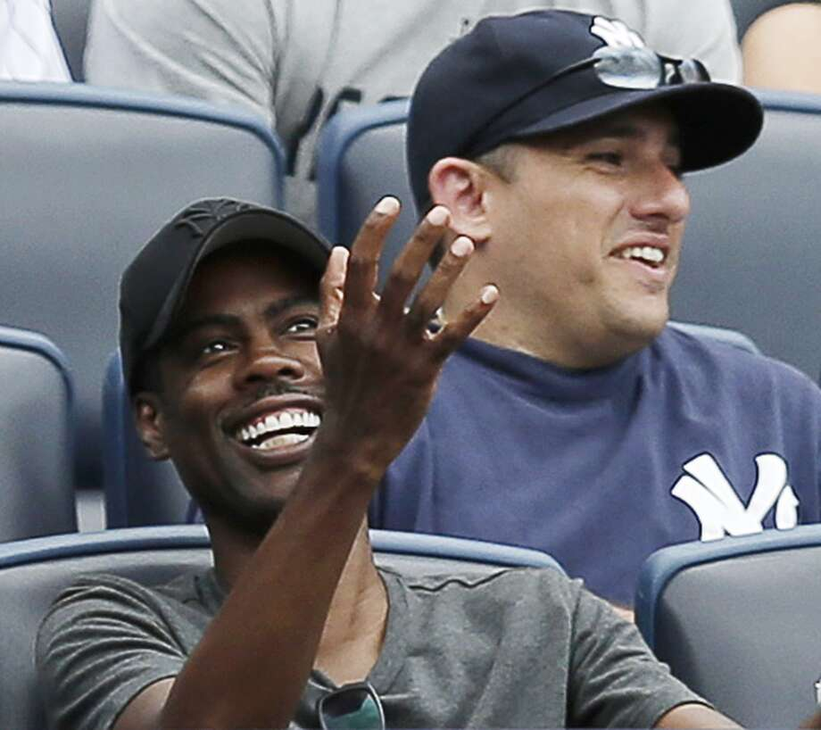 Chris Rock, left, reacts after catching a foul ball off of Astros' Jon Singleton in the seventh inning. Photo: Kathy Willens, Associated Press