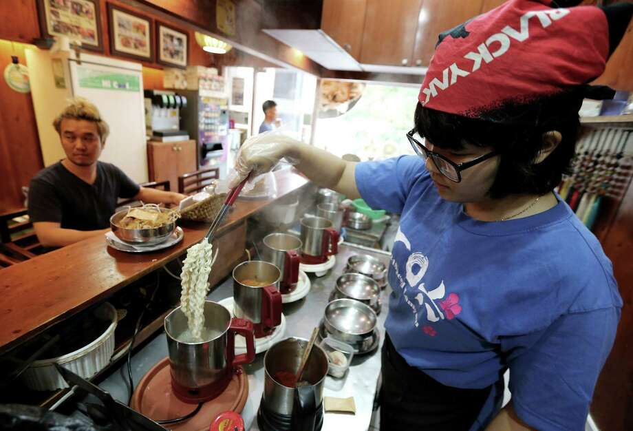 """In this Aug. 19. 2014 photo, a cook prepares """"ramyeon"""" instant noodles for Han Seung-youn, left, during an interview at a ramyeon restaurant in Seoul, South Korea. Instant noodles are an essential, even passionate, part of life for many in South Korea and other Asian countries. Hence the emotional heartburn caused by a Baylor Heart and Vascular Hospital study in the United States that found excessive consumption of instant noodles by South Koreans was associated with risks for diabetes, heart disease or stroke. The study has provoked feelings of wounded pride, mild guilt, stubborn resistance, even nationalism among South Koreans, who eat more instant noodles per capita than anyone in the world. (AP Photo/Ahn Young-joon ) Photo: Ahn Young-joon, STF / AP"""