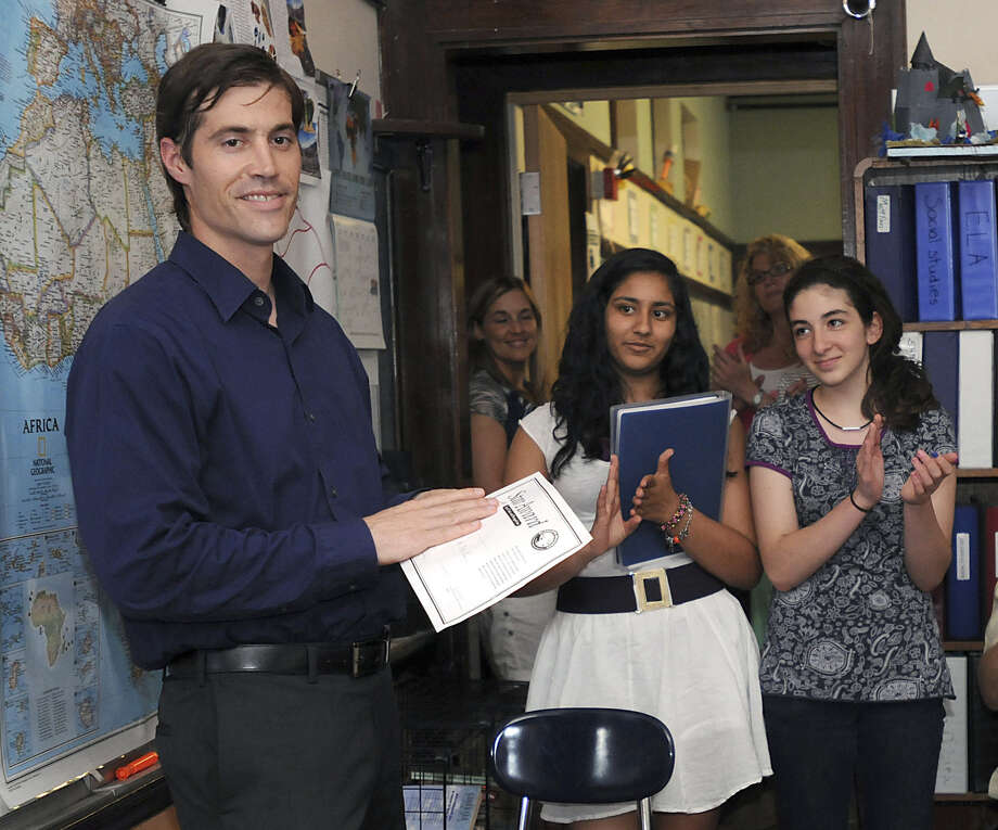 In 2011, journalist James Foley receives applause from students at a school in Framingham, Mass. Foley had been released a month prior after being detained for six weeks in Libya. Photo: Associated Press / MetroWest Daily News