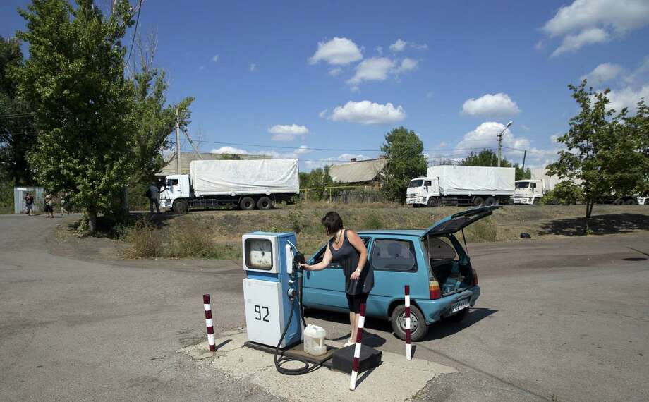A woman fills a can with fuel as part of the Russian aid convoy trucks are parked along a road near a border control point with Ukraine. The trucks, part of a 200-vehicle convoy, are expected to cross into Ukraine this morning. Photo: Pavel Golovkin, Associated Press / AP