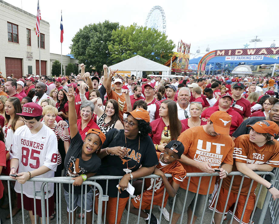 OU and UT fans flash different versions of the same signal while waiting for the teams to arrive at the Cotton Bowl in 2013. Photo: Edward A. Ornelas / San Antonio Express-News / © 2013 San Antonio Express-News
