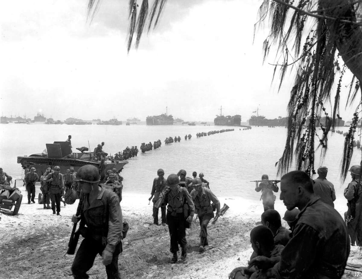 FILE - This July 1944 file photo shows U.S. Army reinforcement troops making an amphibious landing on the coral reef at Saipan beach, Mariana Islands. Racing against time, members of a Japanese organization are combing a New York military museum's World War II records for information they hope will lead to the graves of American servicemen still listed as missing in action on Saipan. (AP Photo, File)
