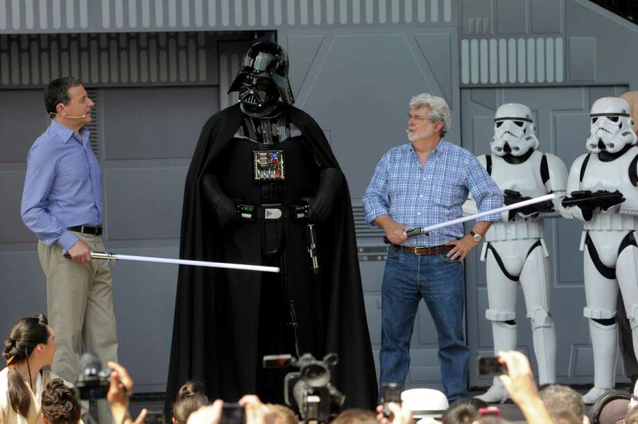 "Darth Vader was flanked by Disney CEO Robert Iger, left, and ""Star Wars"" creator George Lucas in May 2011 at the Disney Hollywood Studios theme park for the reopening of the Star Tours ride in Lake Buena Vista, Fla. Photo: Phelan M. Ebenhack, FRE / FR121174 AP"