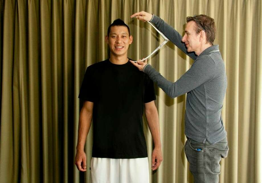 An artist takes a measurement of Jeremy Lin, one of more than 200 it took to create the lifelike figure. Photo: Beck Diefenbach, Madame Tussauds