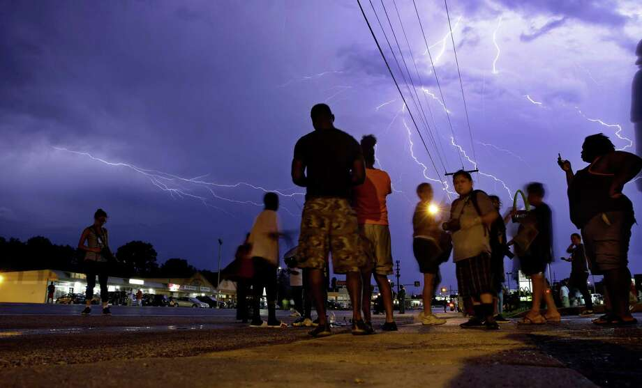 Protesters stand in the street as lightning flashes in the night sky in Ferguson, Mo. on Wednesday, Aug. 20, 2014. A grand jury has begun hearing evidence as it weighs possible charges against the Ferguson police officer who fatally shot 18-year-old Michael Brown. (AP Photo/Jeff Roberson) ORG XMIT: MOJR106 Photo: Jeff Roberson / AP