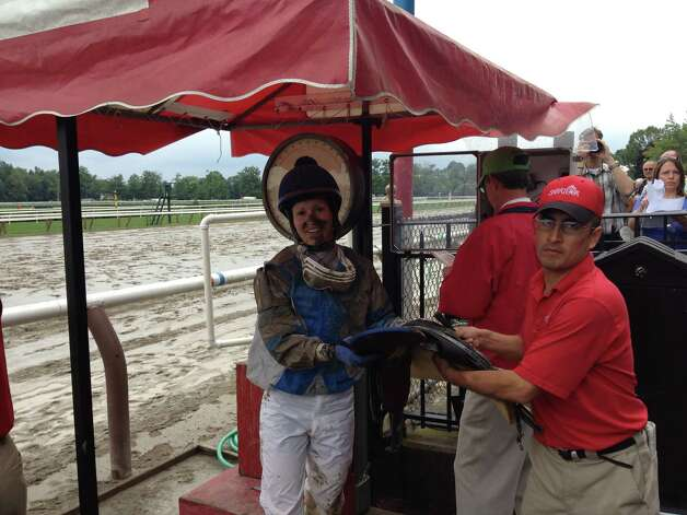 Thursday was one of those rare days of the Saratoga summer when the weather wasn't a racing fan. Early morning downpours left the Saratoga track a sea of slop, and the jockeys were in for a mud bowl all afternoon. Take a look at rider Taylor Rice, who is weighing in after finishing third in the featured Union Avenue Stakes aboard Make the Moment. Her smile tells you that it wasn't all that bad out there —Tim Wilkin