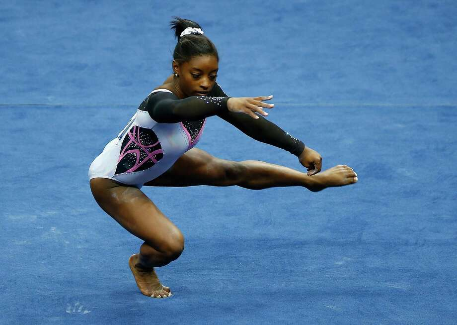 "Simone Biles of Spring set the standard in the floor exercise Thursday night, earning the top score of 15.65 with her high-energy ""carnival style"" routine. Photo: Jared Wickerham, Stringer / 2014 Getty Images"