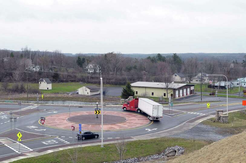 A tractor trailer is maneuvered through a roundabout as it travels towards the bypass just off exit