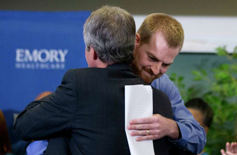 Ebola victim Dr. Kent Brantly, right, hugs a member of the medical staff that treated him, after being released from Emory University Hospital Thursday, Aug. 21, 2014, in Atlanta. Another American aid worker, Nancy Writebol, who was also infected with the Ebola virus, was released from the hospital Tuesday. (AP Photo/John Bazemore) ORG XMIT: GAJB104 Photo: John Bazemore / AP