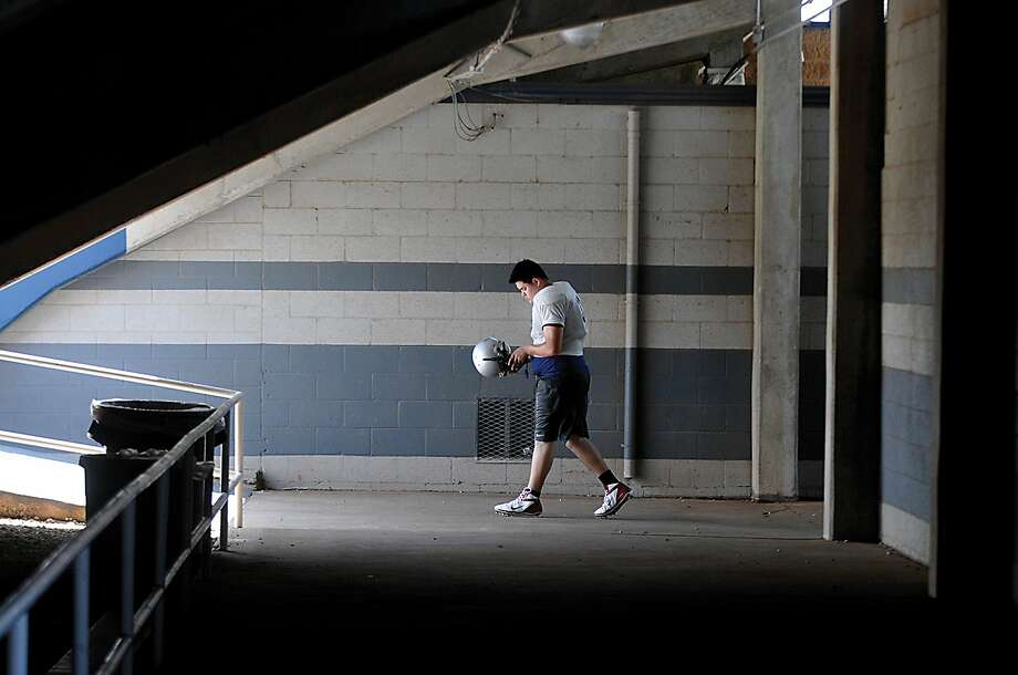 An Enid High football player heads to the turf of D. Bruce Selby Stadium to begin practice Thursday August 21, 2014 in Enid, Oklahoma. (AP/Enid News & Eagle, Billy Hefton) Photo: Bh, Associated Press