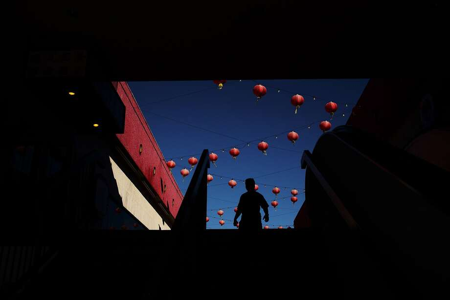 A shopper is silhouetted as he walks through a mall adorned with some Chinese lanterns, Thursday, Aug. 21, 2014, in the Chinatown section of Los Angeles. It is one of the oldest, largest and most historic Chinatowns in the U.S. (AP Photo/Jae C. Hong) Photo: Jae C. Hong, Associated Press