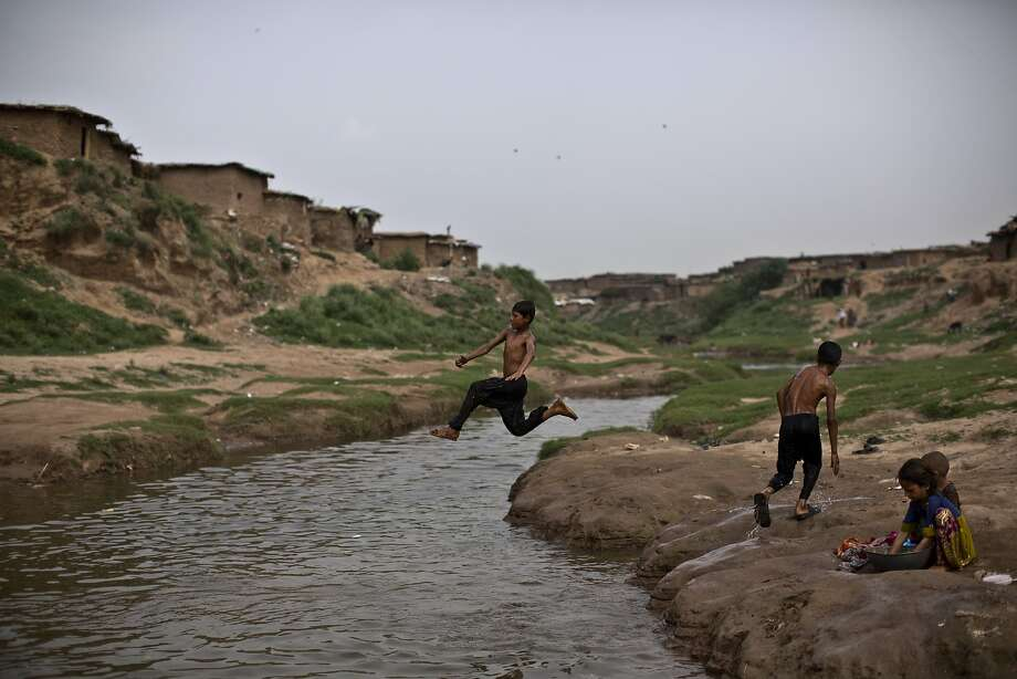 An Afghan refugee boy, jumps into the water, while he and others swim in a polluted stream to cool off as the temperature rises, on the outskirts of Islamabad, Pakistan, Thursday, Aug. 21, 2014. (AP Photo/Muhammed Muheisen) Photo: Muhammed Muheisen, Associated Press