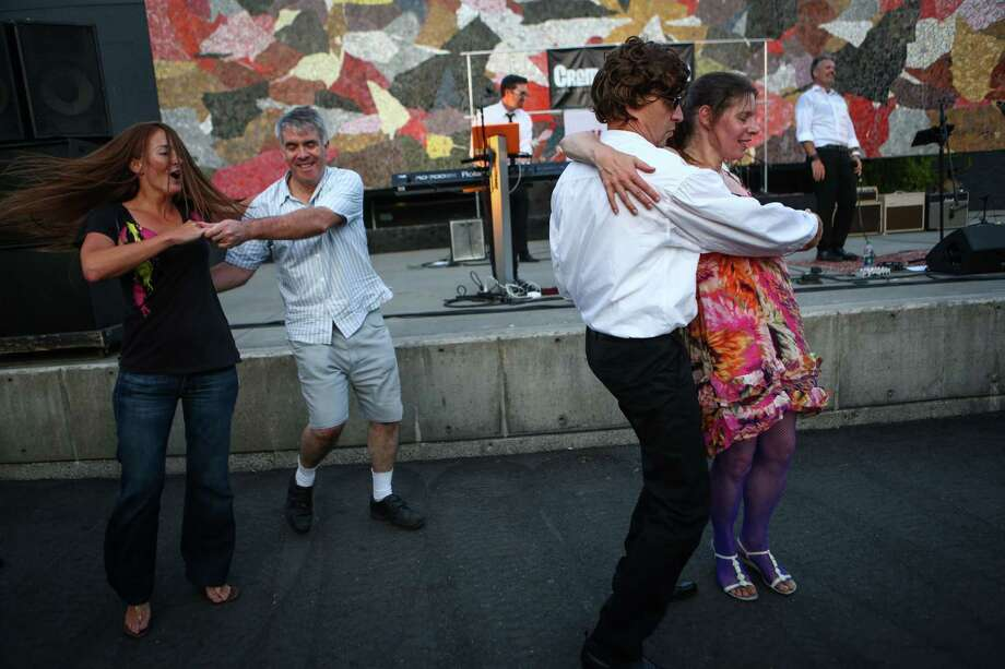 People dance as The Beatles cover band Creme Tangerine performs at Seattle Center's Mural Amphitheater on Thursday, Aug.12, 2014. The band performed on the 50th anniversary of The Beatles Seattle Center performance. Photo: JOSHUA TRUJILLO, SEATTLEPI.COM / SEATTLEPI.COM