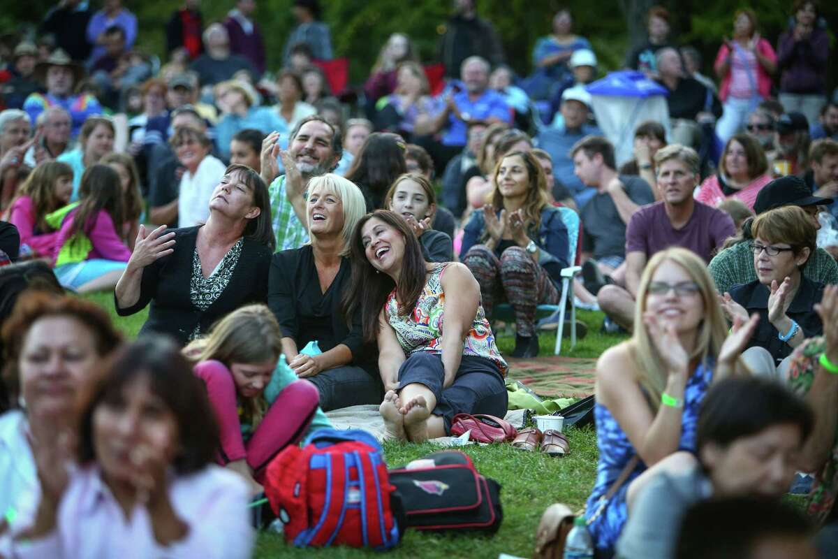 Spectators sing along as The Beatles cover band Creme Tangerine performs at Seattle Center's Mural Amphitheater on Thursday.
