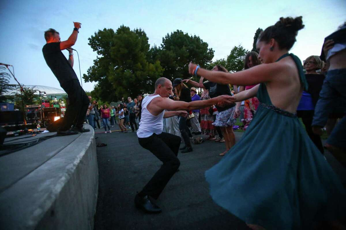 People dance as The Beatles cover band Creme Tangerine performs at Seattle Center's Mural Amphitheater on Thursday.
