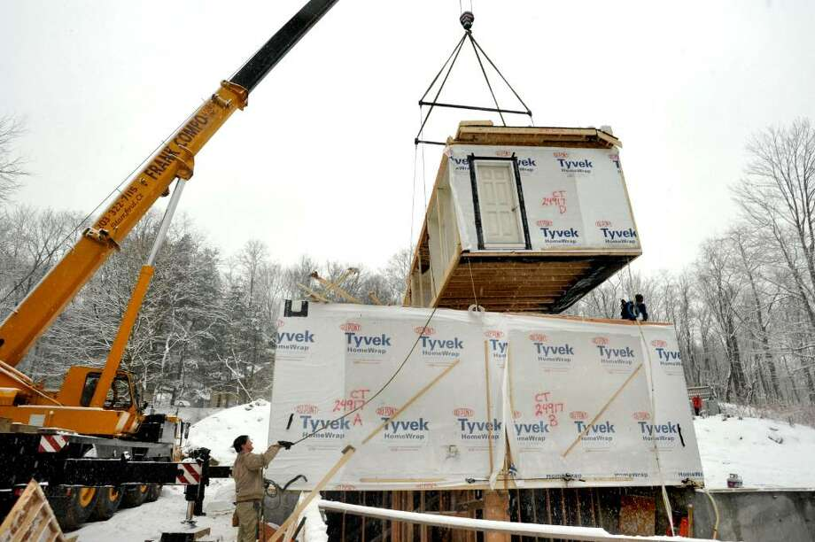 Builder Kevin Coyle, 46, guides the second level of the new modular home as it is lifted, at the construction site in Redding, on Tuesday, Feb.16,2010. Photo: Michael Duffy / The News-Times
