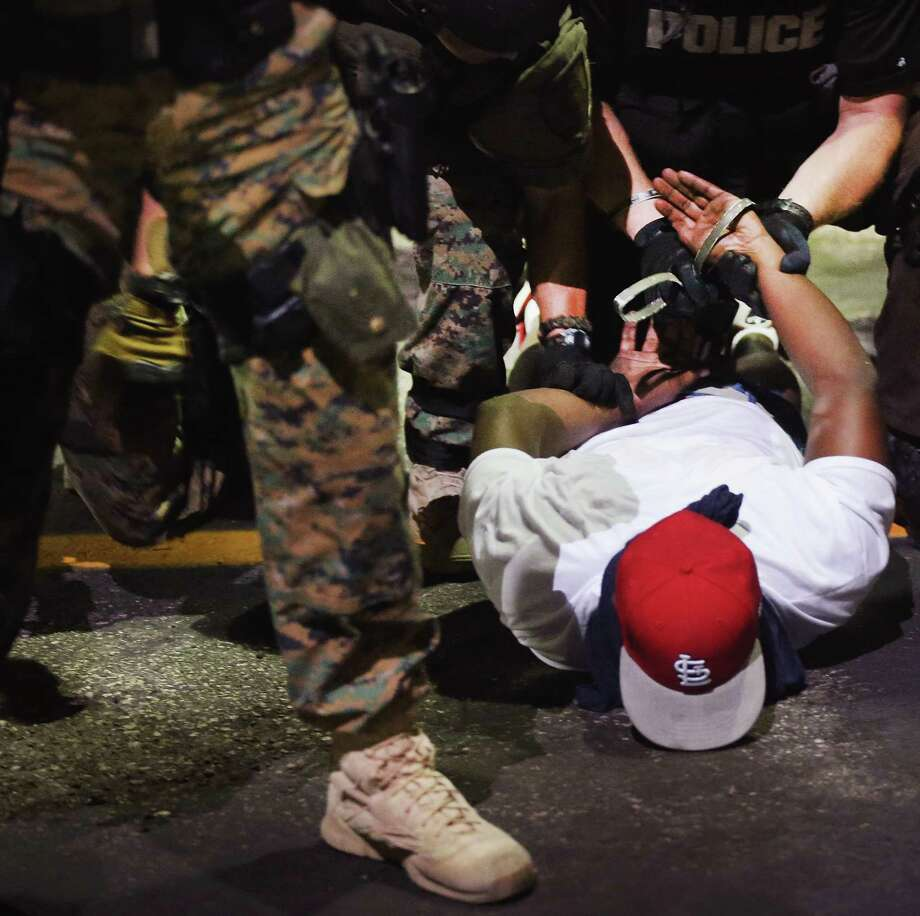FERGUSON, MO - AUGUST 19:  Police arrest a demonstrator protesting the killing of teenager Michael Brown on August 19, 2014 in Ferguson, Missouri. Brown was shot and killed by a Ferguson police officer on August 9. Despite the Brown family's continued call for peaceful demonstrations, violent protests have erupted nearly every night in Ferguson since his death.  (Photo by Scott Olson/Getty Images) Photo: Scott Olson, Staff / Getty Images / 2014 Getty Images