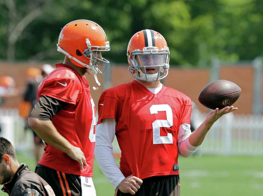 Cleveland Browns quarterback Johnny Manziel (2) talks with Brian Hoyer during practice at the NFL football team's facility in Berea, Ohio Wednesday, Aug. 20, 2014. Earlier head coach Mike Pettine names Hoyer as the regular season starter against the Steelers in Pittsburgh. Photo: Mark Duncan, AP / AP