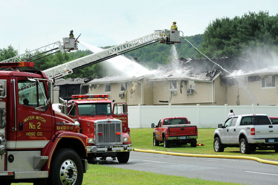 Firefighters work to control a fire that spread through several units of a condominium complex on Danbury Rd., in New Milford, Conn. Aug. 21, 2014. Photo: Ned Gerard / Connecticut Post