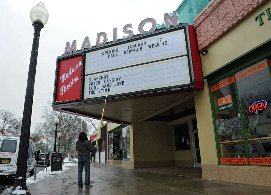 "Madison Theatre employee Joseph Alindato of Albany places information on the marquee on Thursday, Jan. 16, 2014 in Albany, N.Y. Friday is the grand re-opening of the theatre and will start with classic Paul Newman flicks such as ""Slapshot,"" ""Butch Cassidy and the Sundance Kid,"" Cool Hand Luke"" and ""The Sting."" (Lori Van Buren / Times Union) Photo: Lori Van Buren / 00025401A"