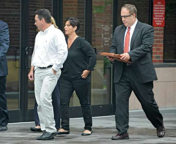 Bruce Tanski's secretary Katina Fogarty, center, leaves the Saratoga County Courthouse with her attorney John Sweeney, right, after her arraignment on a charged with a single count of concealing the true origin of a campaign donation on Friday, Aug. 22, 2014 in Ballston Spa, N.Y. Tanski, a prominent Halfmoon builder, was arrested by State Police on charges alleging he paid employees and business associates to make political contributions to the campaign account of Melinda Wormuth, a former Halfmoon town supervisor. (Lori Van Buren / Times Union) Photo: Lori Van Buren / 00028289A