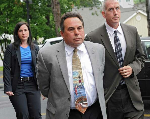 Nicholas DiNova Jr., center, an employee of Troy Sand & Gravel who lives in a home Bruce Tanski built, is brought to the Saratoga County Courthouse in custody by FBI agents and state attorney generals investigators and is being charged with a single count of concealing the true origin of a campaign donation on Friday, Aug. 22, 2014 in Ballston Spa, N.Y. Bruce Tanski, a prominent Halfmoon builder, was arrested by State Police on charges alleging he paid employees and business associates to make political contributions to the campaign account of Melinda Wormuth, a former Halfmoon town supervisor. (Lori Van Buren / Times Union) Photo: Lori Van Buren / 00028289A